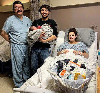 Doctor with newborn and parents